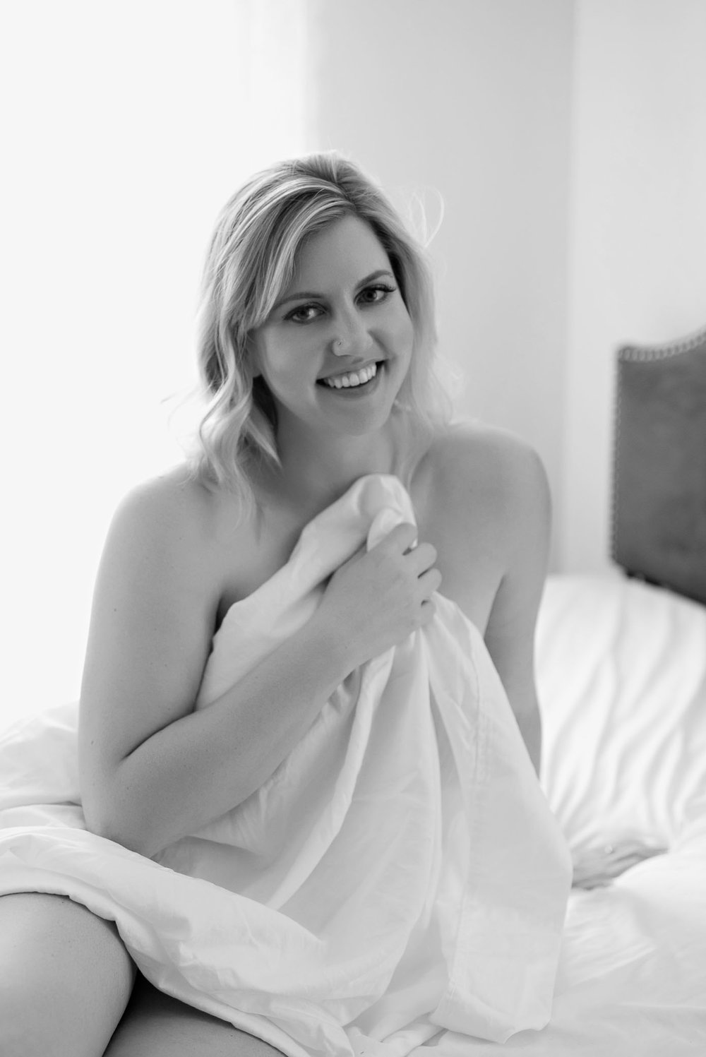 White sheet boudoir session smiling blonde holding sheet