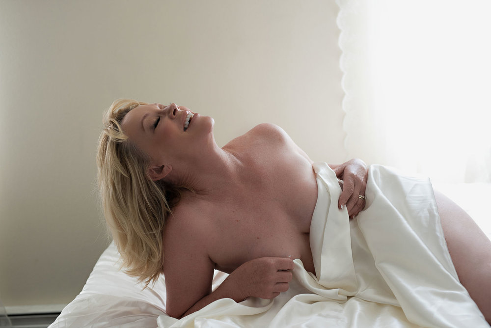Denver white sheet boudoir photo of smiling blonde woman