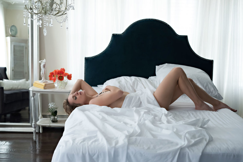 Woman laying across bed in boudoir pose wrapped in white sheet