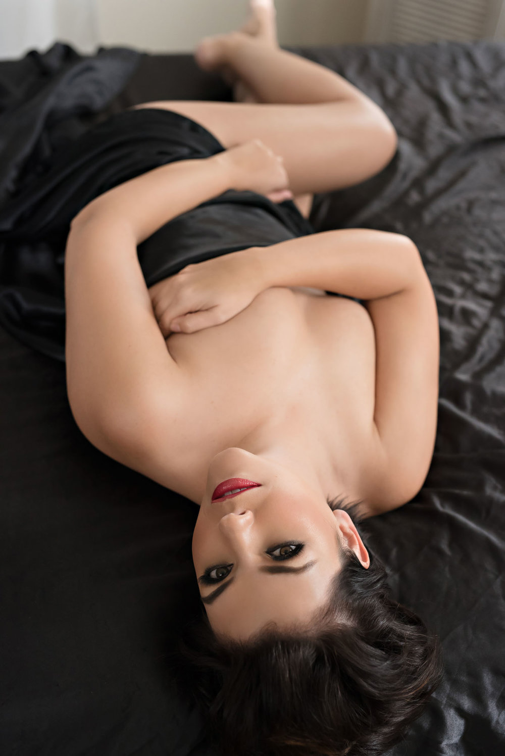 Sexy boudoir photo shoot in black sheets