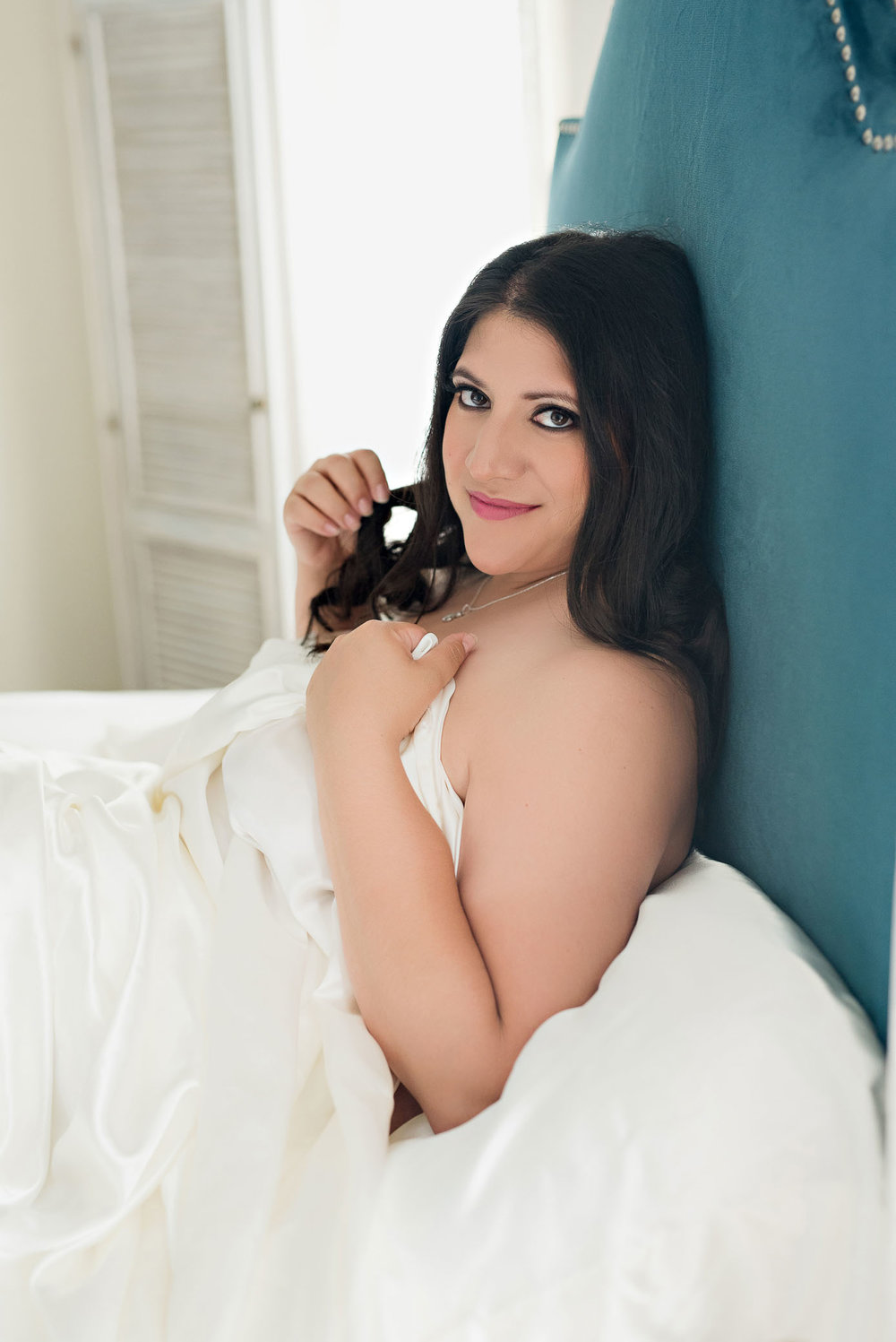 Smiling plus size woman white sheet boudoir photography