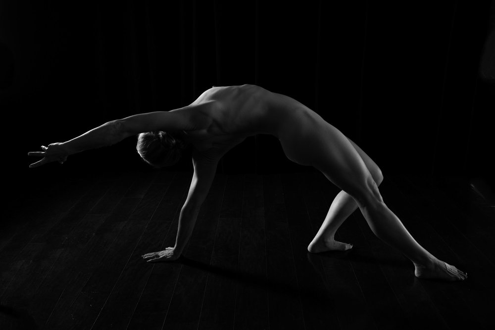 low key black and white art nude of woman in yoga pose