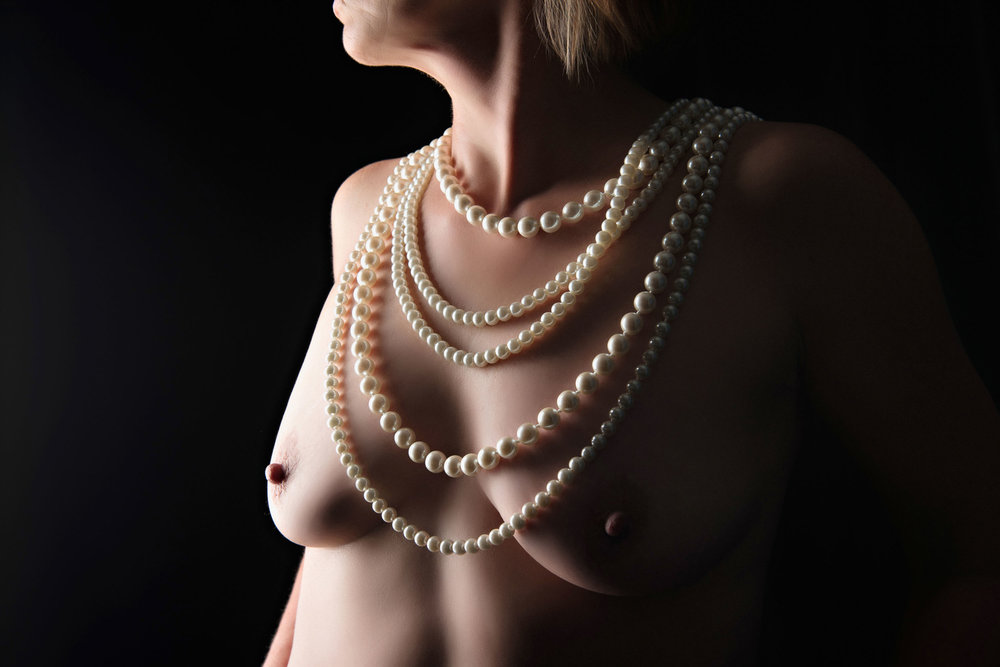 Older woman wearing pearls in art nude photography
