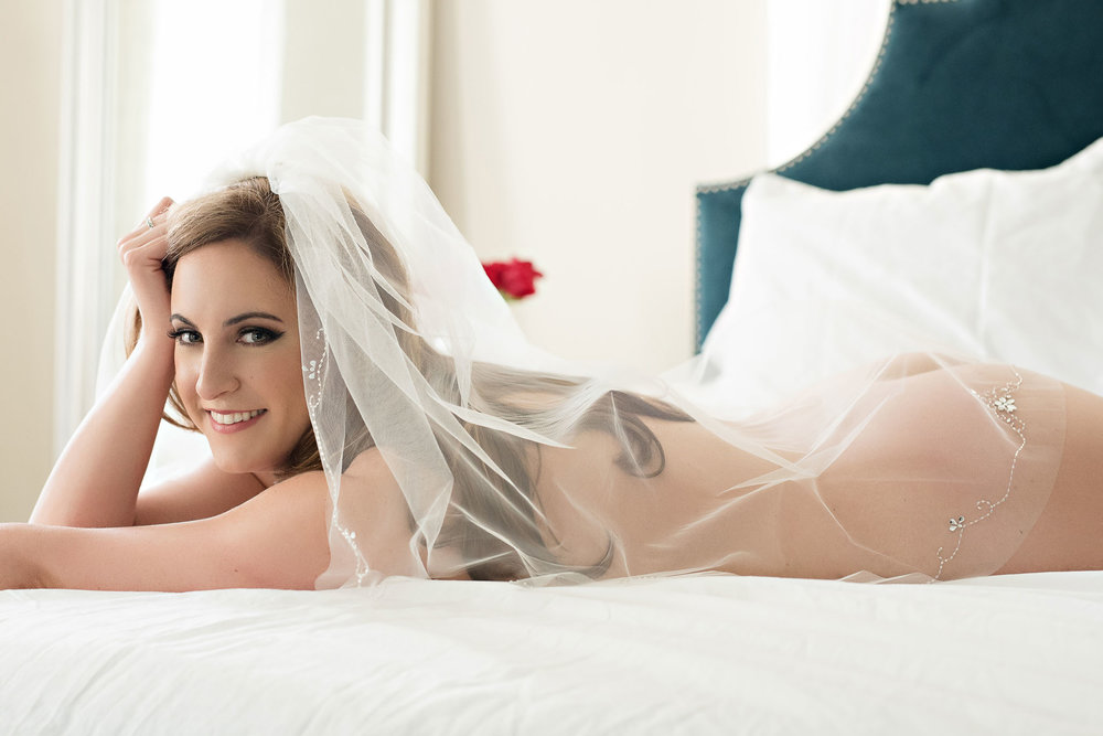 Smiling bride laying on bed Denver Colorado bridal boudoir photography studio