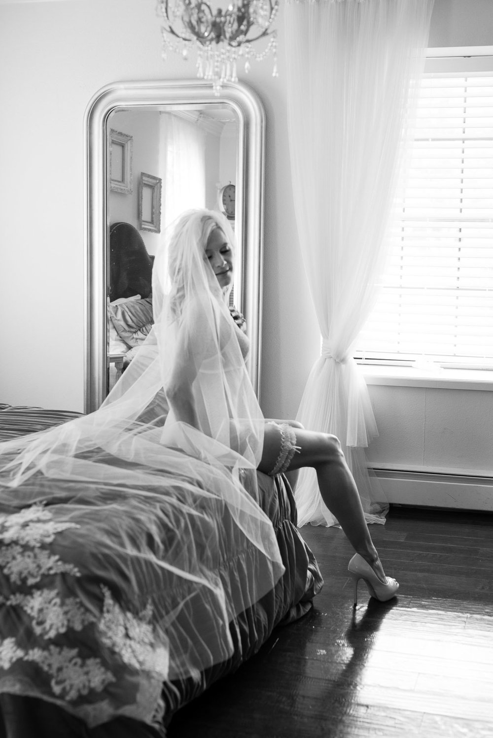 Bridal boudoir photo of fit blonde woman in veil at Colorado boudoir photographer studio