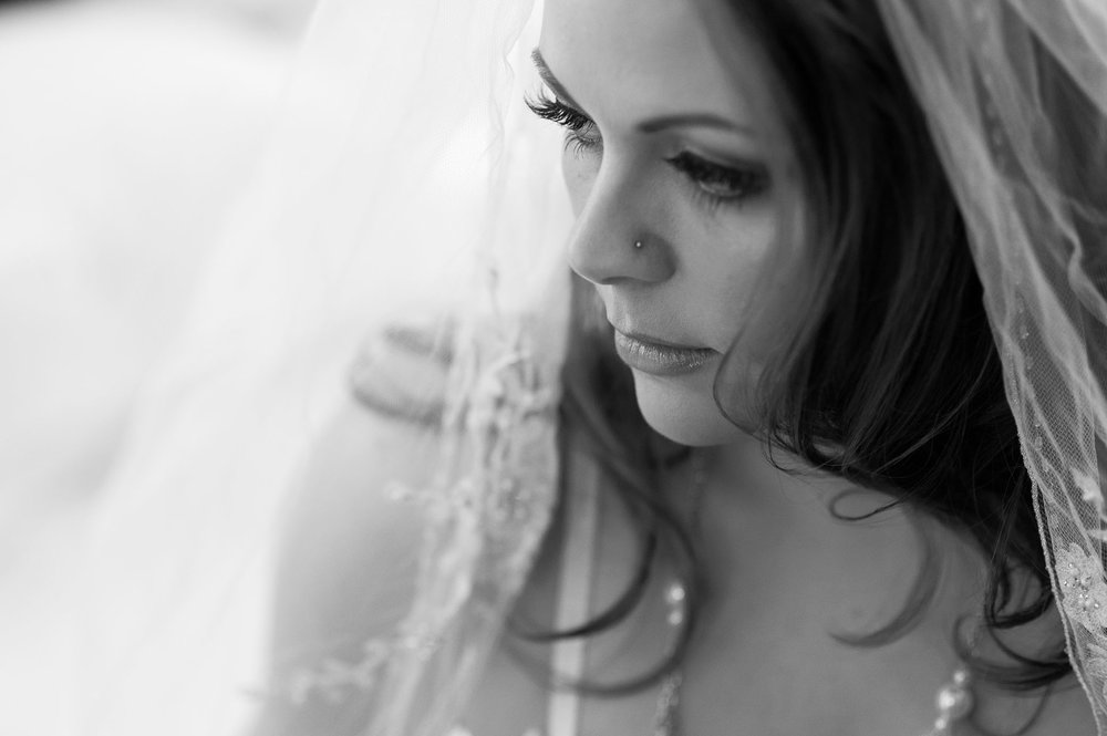 Black and white bridal boudoir photo of young woman wearing pearls and veil in Denver boudoir studio