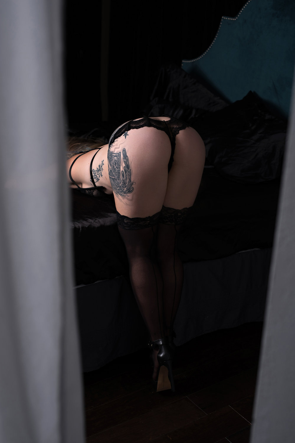 Steampunk boudoir session photo of tattooed woman wearing black lingerie and stockings
