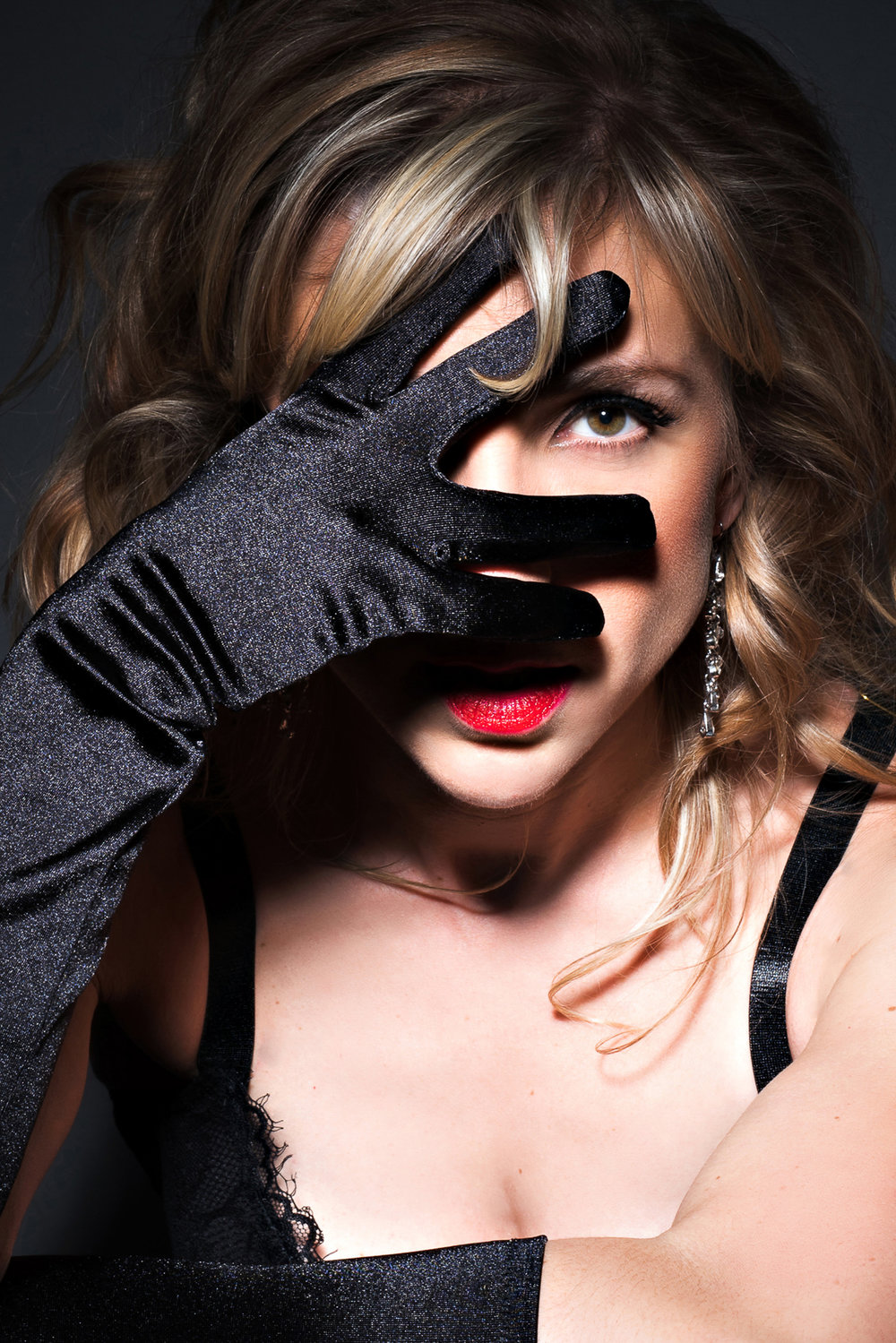 Denver boudoir photo of Blonde woman covering face with lack satin gloved hand