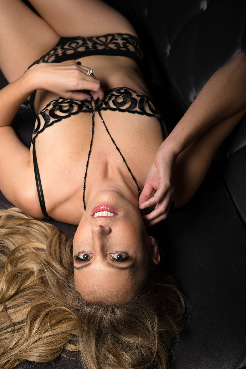 fit blonde woman wearing black boudoir outfit in Denver photographer studio