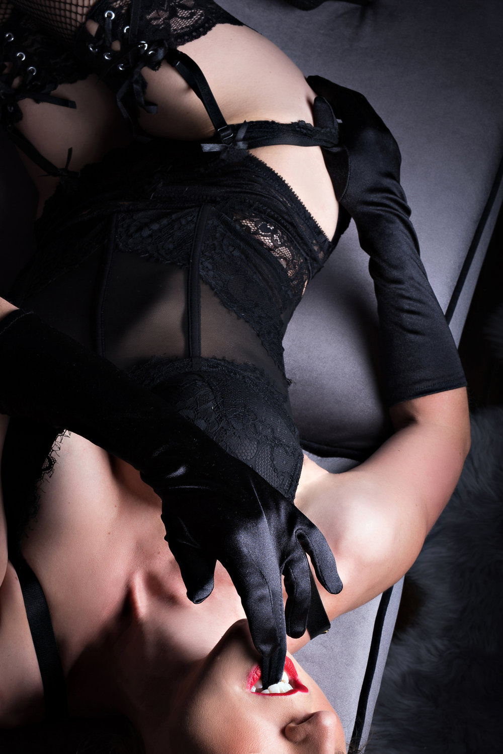 Denver boudoir photo of woman in sexy black lingerie and gloves biting finger seductively
