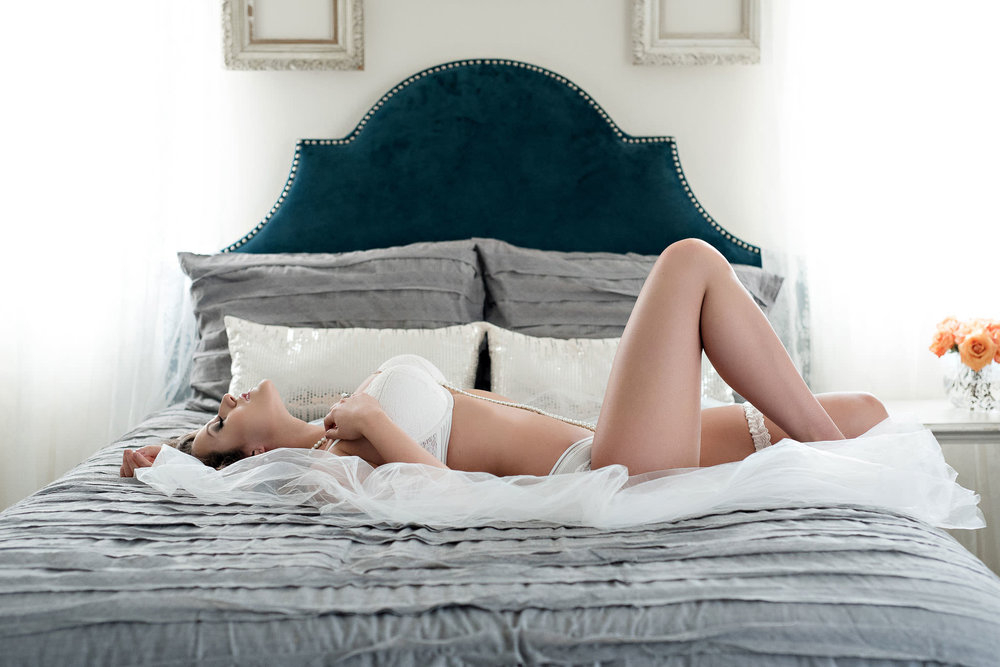Bride on bed in white lingerie boudoir photo