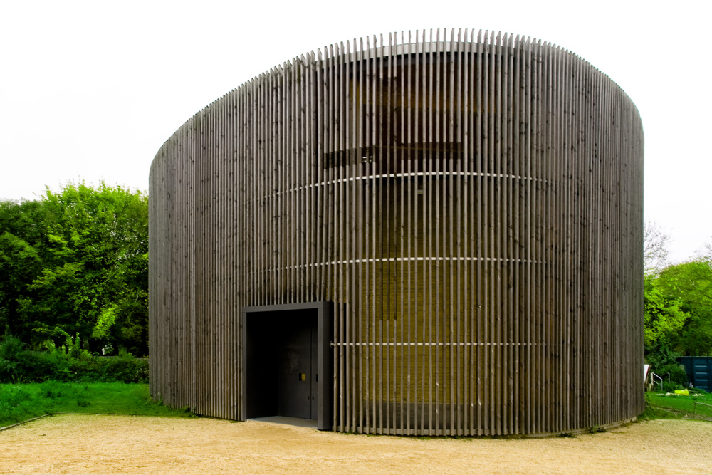Timber slatted external shell embraces the oval shape of the internal rammed earth structure.