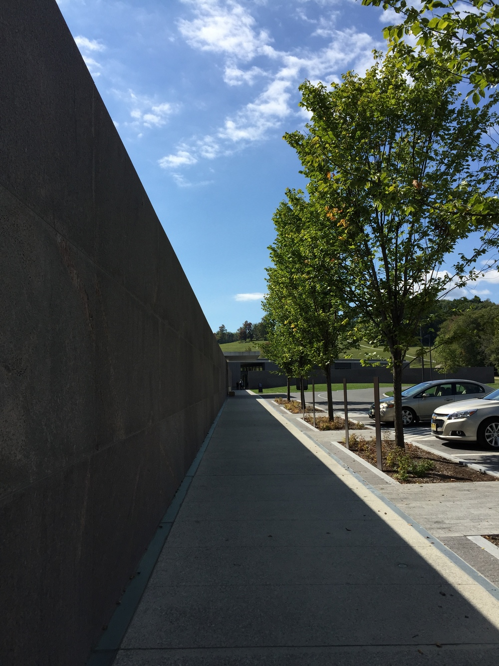 An extended red granite wall draws visitors down a long line of procession from car park to entrance