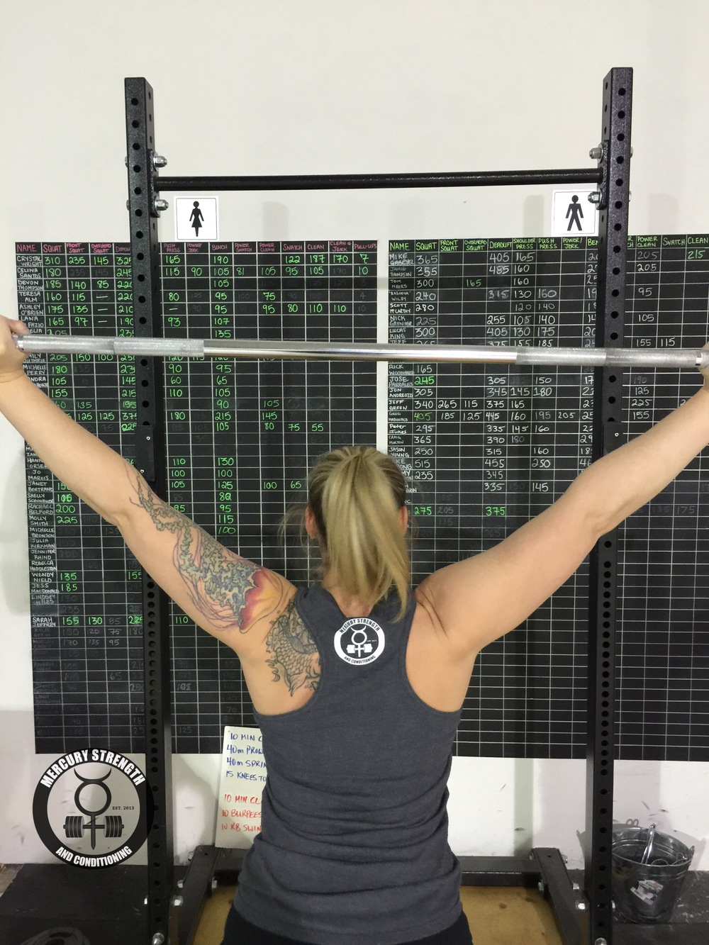 Coach Lindsey with some overhead work sporting the Mercury Strength grey racerback. Also available in a cranberry colour. get yours now!