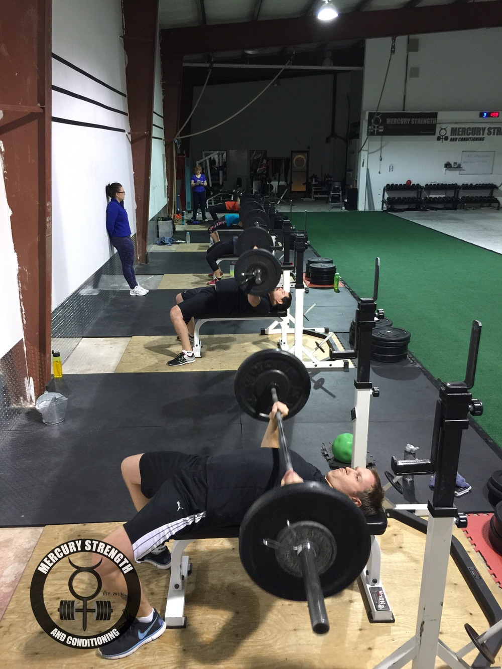 06:30 crew doing a set of 10 for bench press while Michelle supervises.