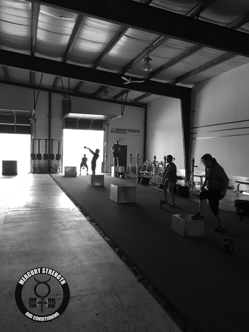 Kettlebell swings and box jumps being performed during Tuesday's workout.