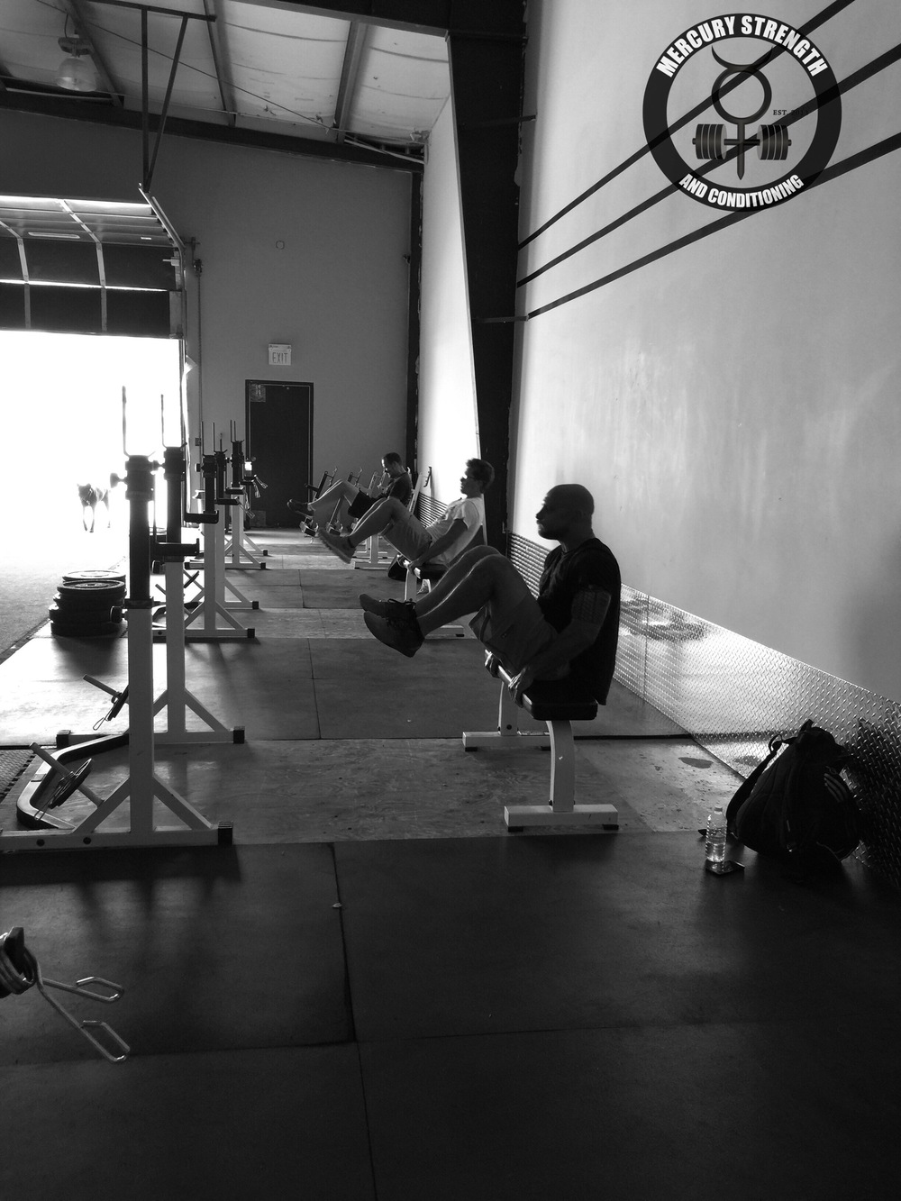 Sean, Chris, and Andrew performing some v-crunches during a humid morning session.