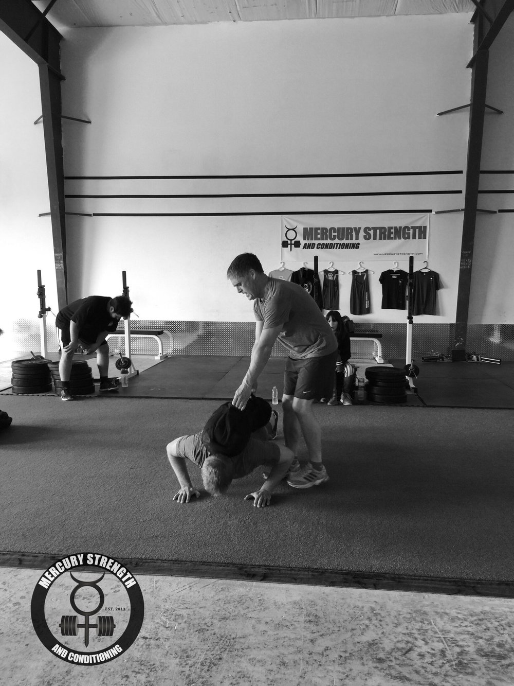 Paul balancing the sandbag for Lucas during some weighted push-ups