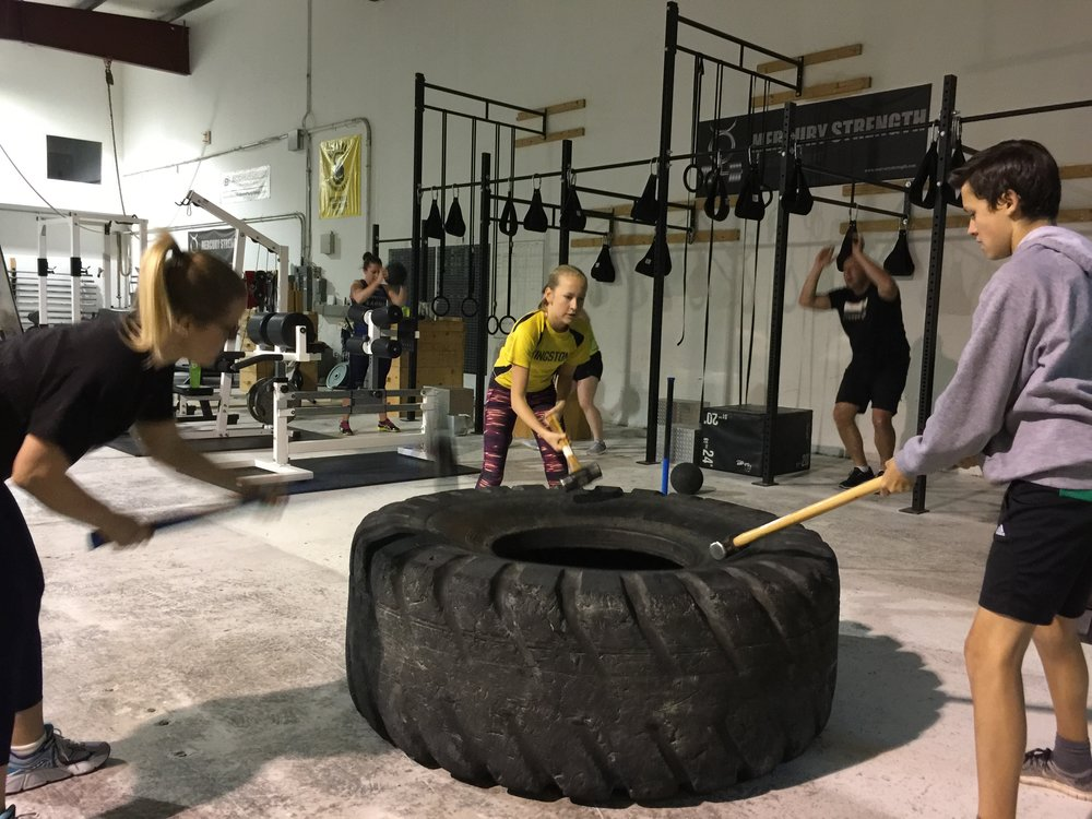 Morgan, Abby, and Rhys smashing the tire while Catherine and Curtis are repping out some burpees and slam balls