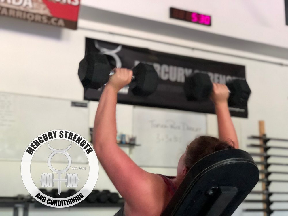 Catherine repping out some incline DB bench press