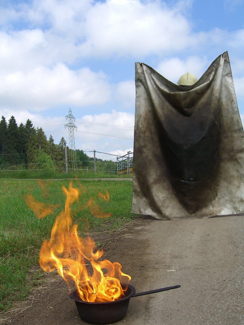 Wie löscht mer richtig ä Flamme, entstande us Öl? - Feuerwehrhelm anziehen und mit den Händen in die dafür vorgesehene Öffnung, dann langsam mit der Löschdecke zur Flamme laufen...