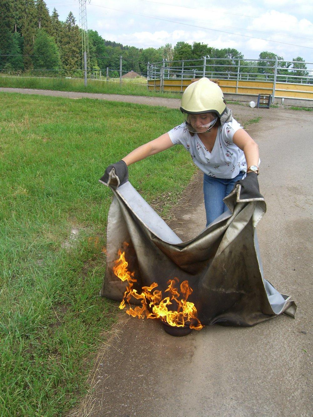 - Vorsichtig die Decke über die Flamme legen. Lange genug auf der Flamme lassen, damit das Feuer sicher erstickt wurde.