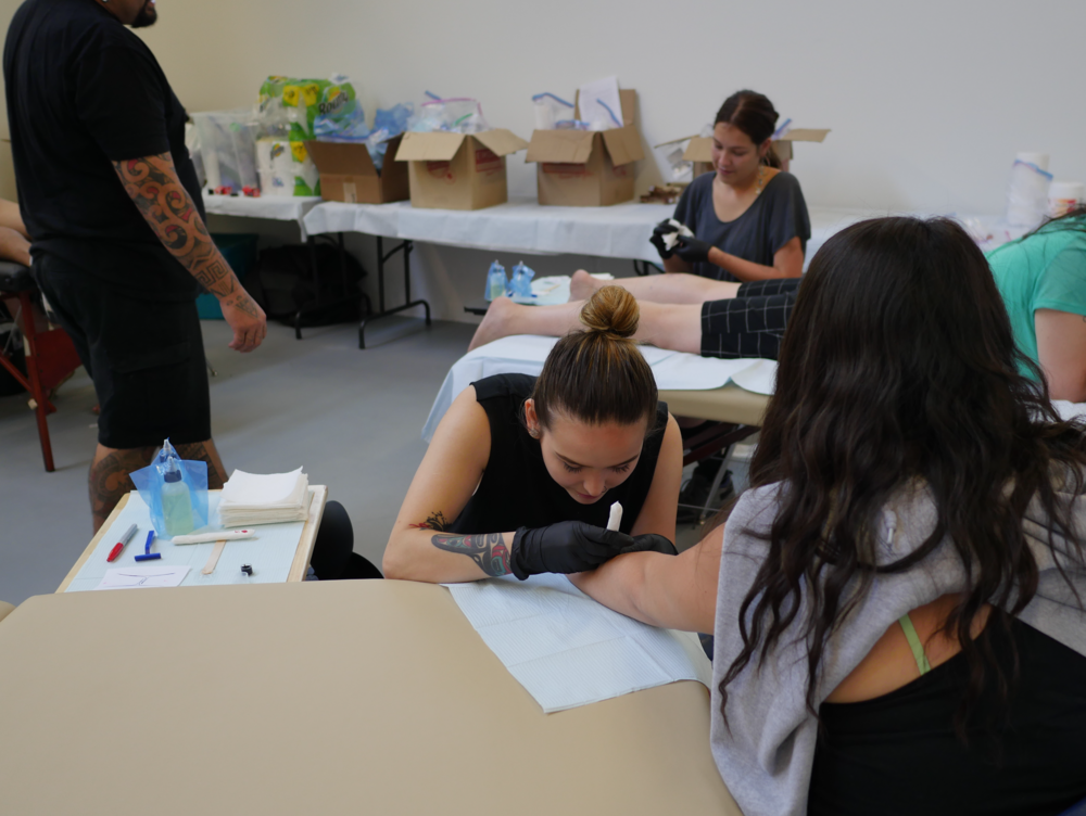 Female tattoo artists are Danika Nacaarella (forefront) and Maannii Oakes (background) .