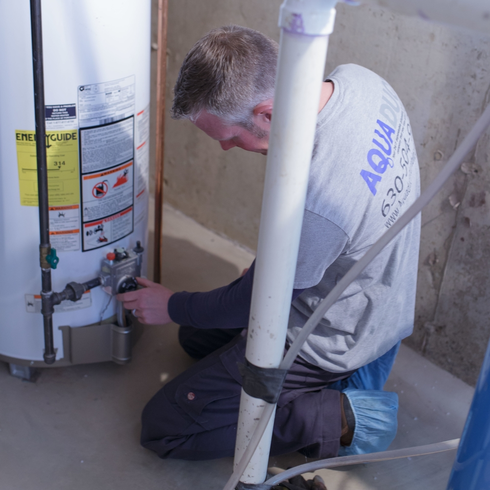 A man performing water heater repairs in Montgomery, IL