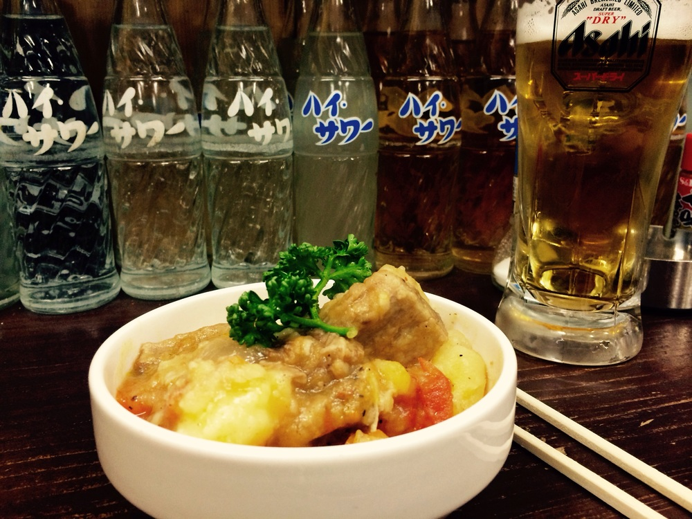 Beef tendon stew with tomato and boiled potato, parsley to garnish.