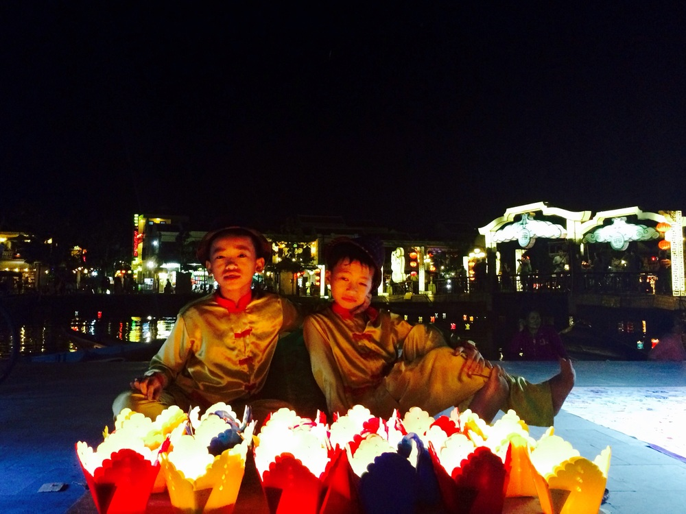 Two unamused kids in Hoi An selling candle lanterns along the river.