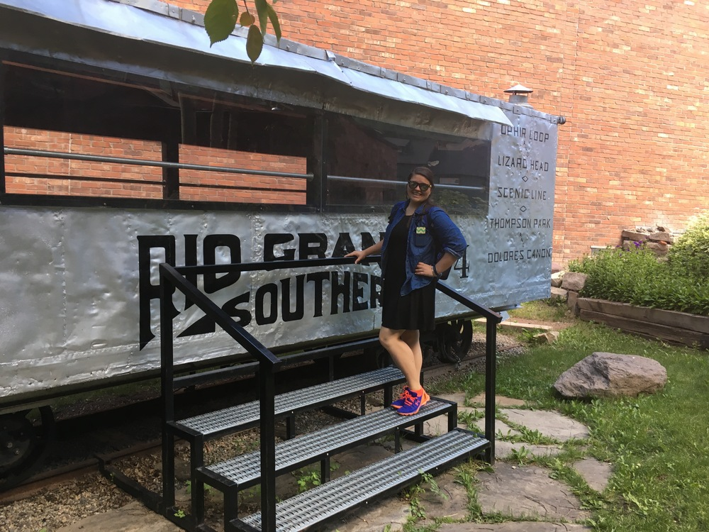 Kara poses with an old train car from the Rio Grande service line.