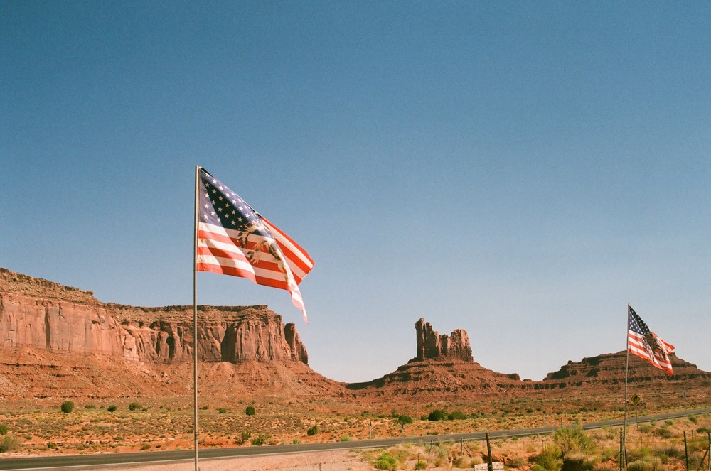 The Navajo Nation and Geronimo flags fly at Monument Valley Navajo Tribal Park. 35 mm film.