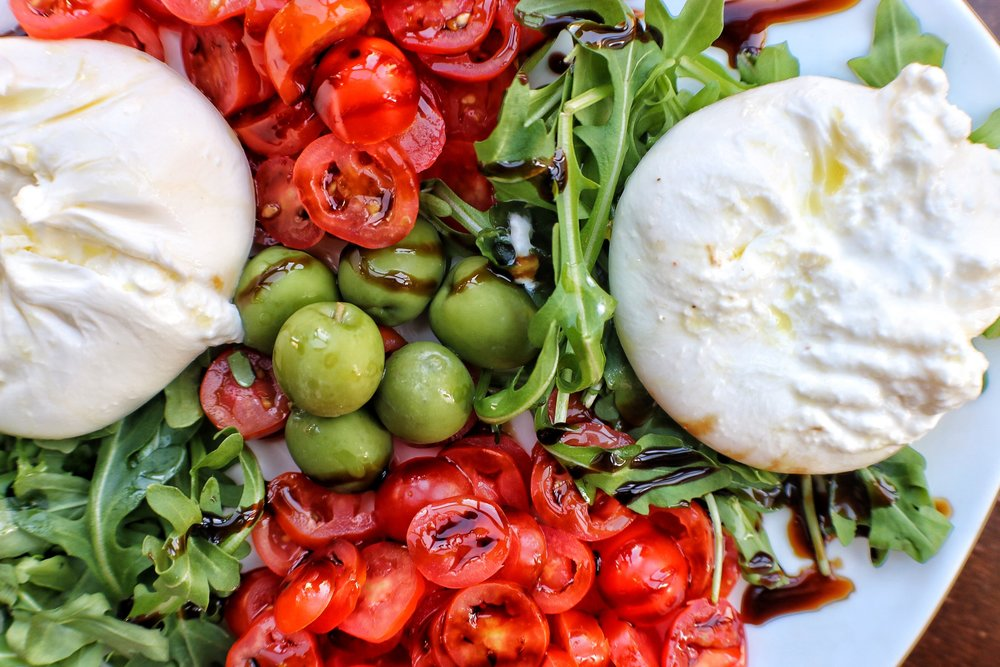 Burrata   Creamy centered Mozzarella served with Arugula, Castelvetrano Olives and Cherry Tomatoes
