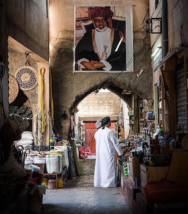Omani alleyways. Sultan Qaboos keeps a watchful eye over the bargaining and haggling in Nizwa's market.
