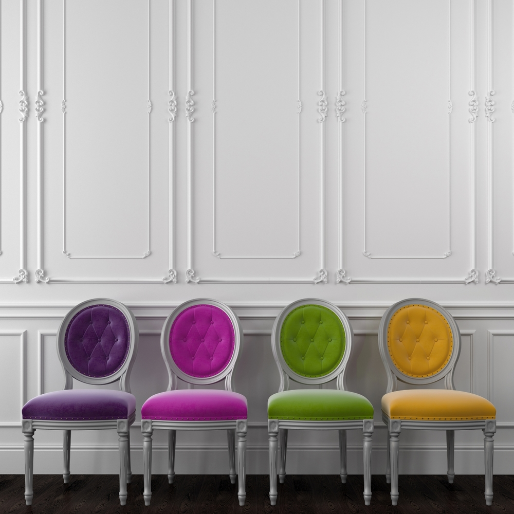 row-of-purple-fuchsia-green-yellow-velvet-chairs-front-of-ornate-white-wall-67009051.jpg