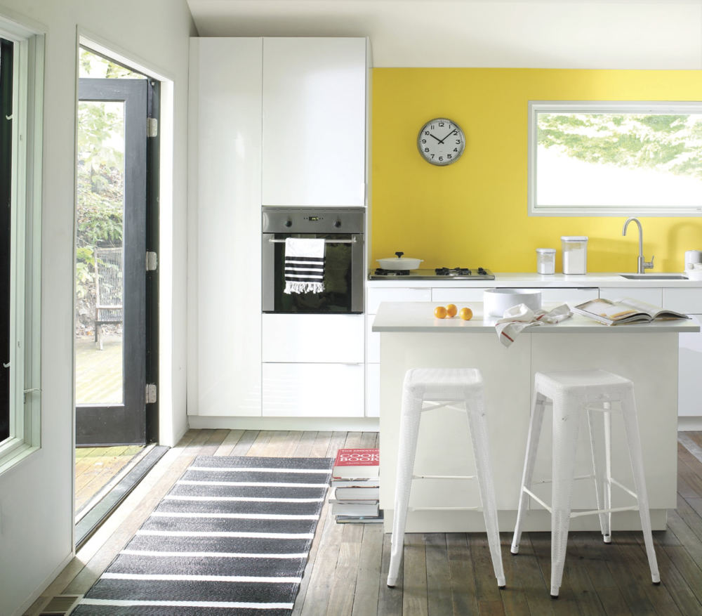 White with a pop of cheerful yellow. Accent wall in Banana Yellow 2022-40, eggshell finish.  Wall and ceiling in Paper White OC-55, eggshell finish. Ceiling in Waterborne Ceiling Paint, ultra-flat finish. Photo: Benjamin Moore.
