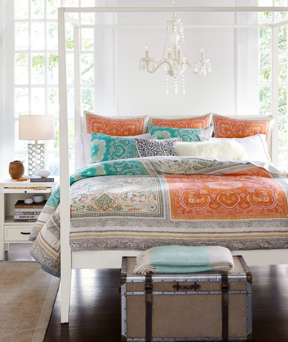Claire Scarf print bedding from Pottery Barn makes a colorful splash in this bedroom along with Lara chandelier made of handblown glass on an iron frame. The Zimmer trunk is a nice accent piece with a mahogany frame accented with hand-hammered aluminum edging and leather handles. Photo: Pottery Barn.