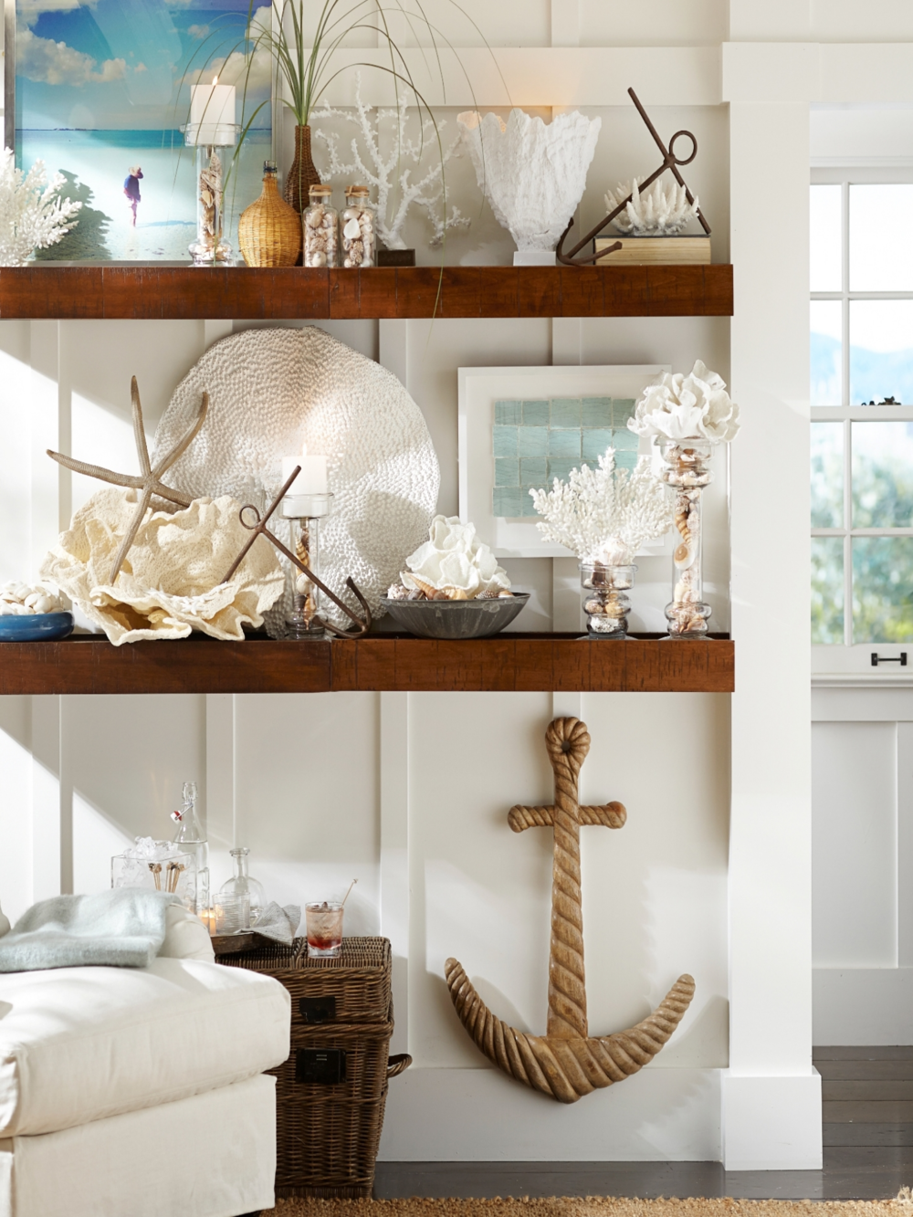 Style a bookcase or shelving with a tropical theme. Incorporate white furnishings, white walls and a jute rug. Photo: Pottery Barn.