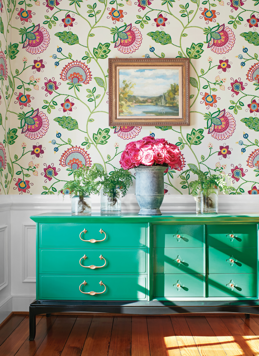 Pretty painted chest set against the backdrop of Thibaut's Portofino wall covering. These large, stylized, flowers and other fun details make this a striking accent wall. The wallpaper is rotary screen printed, which uses a lot of ink to make the flowers slightly textured. Photo credit: Courtesy of Thibaut.  www.thibautdesign.com