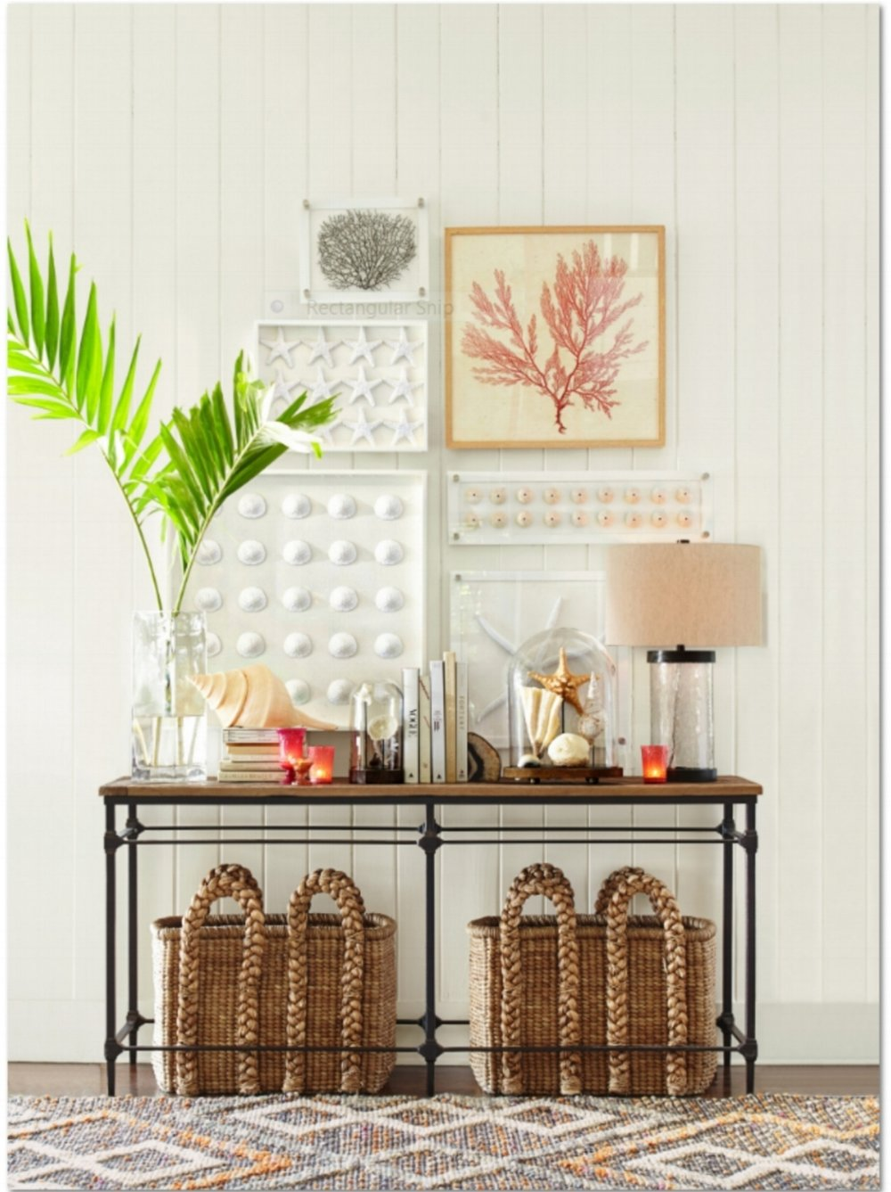 A reclaimed wood console table is the perfect base for building a collection in an entry or family room that reflects the owner of the home. Artwork, greenery, books, lamp and natural touches including natural seagrass beachcomber baskets that are beautiful and perfect for storage. All anchored by a handwoven diamond-wrapped jute rug. Photo courtesy of Pottery Barn.