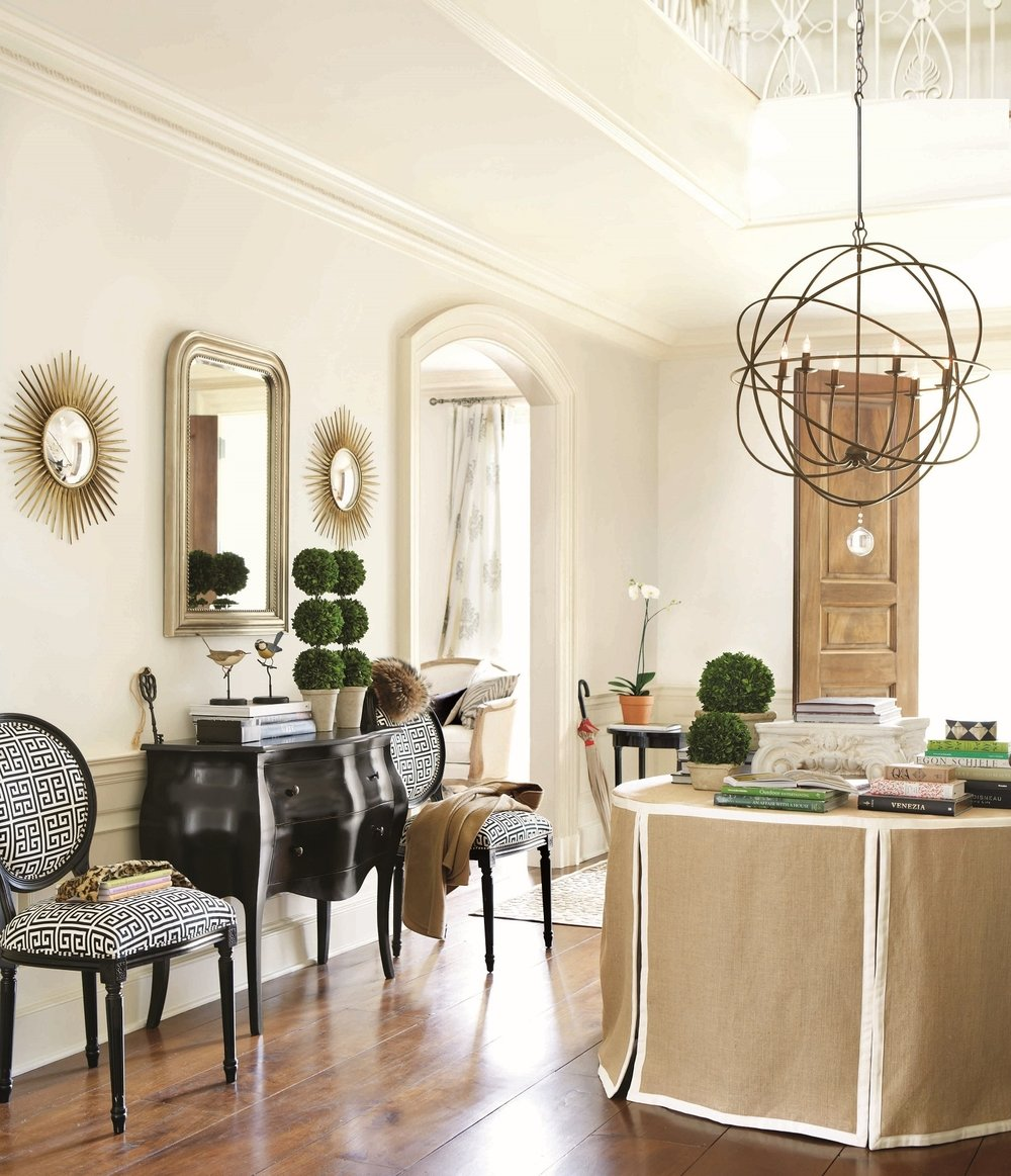 In the classic Louis Philippe style, the iconic rounded shoulders and squared base of this Louis Mirror strike a perfect balance between casual curves and crisply tailored lines. Composite frame with beveled glass. The orb chandelier features an openwork sphere of hand wrought iron surrounding six upright globe lights to illuminate your space in a dining room, living room or entry. Photo courtesy of Ballard Designs.