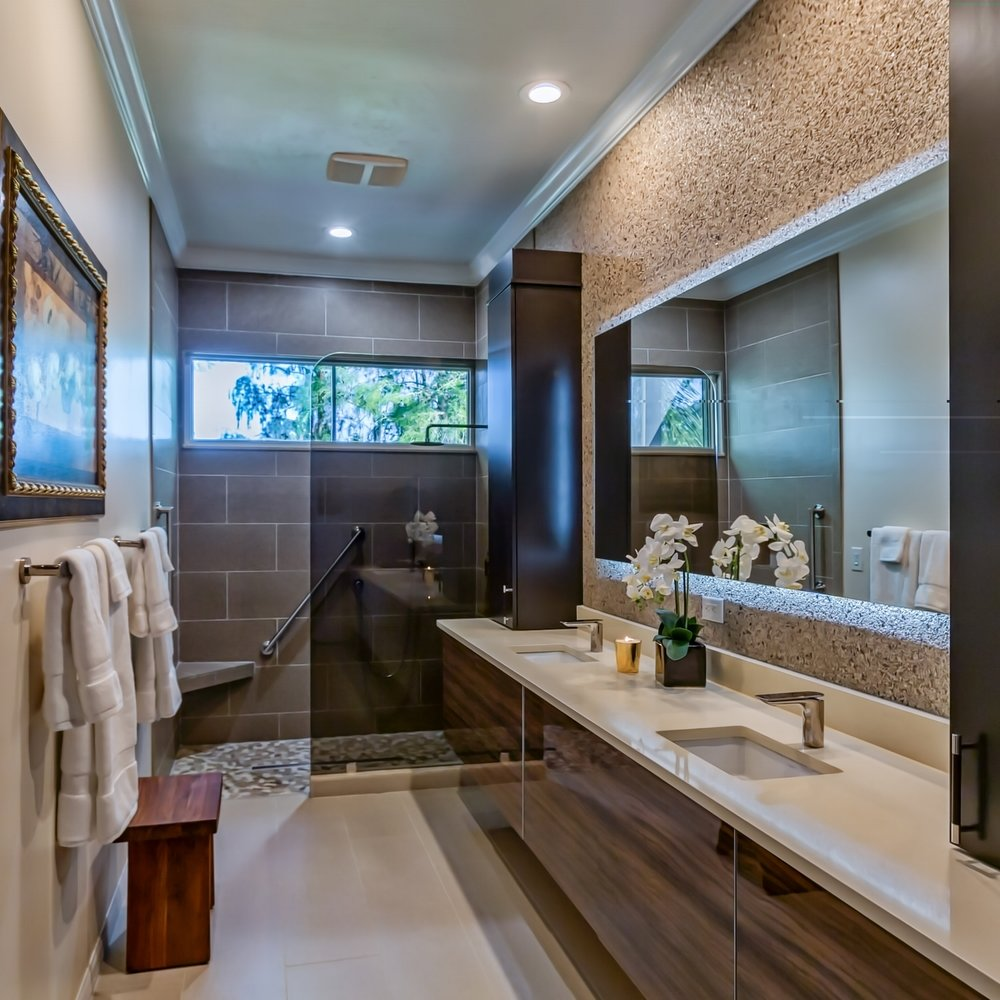 Total redo of this master bathroom with the goal of creating an Asian/Zen retreat for the owners. Quartz countertops, custom veneer vanity in tiger wood, mirror is lit from behind, wall covering, leather handles on cabinets. Flat tile with linen finish on floors. Photos by R.L. Caron. Courtesy of Diane Torrisi Designs.