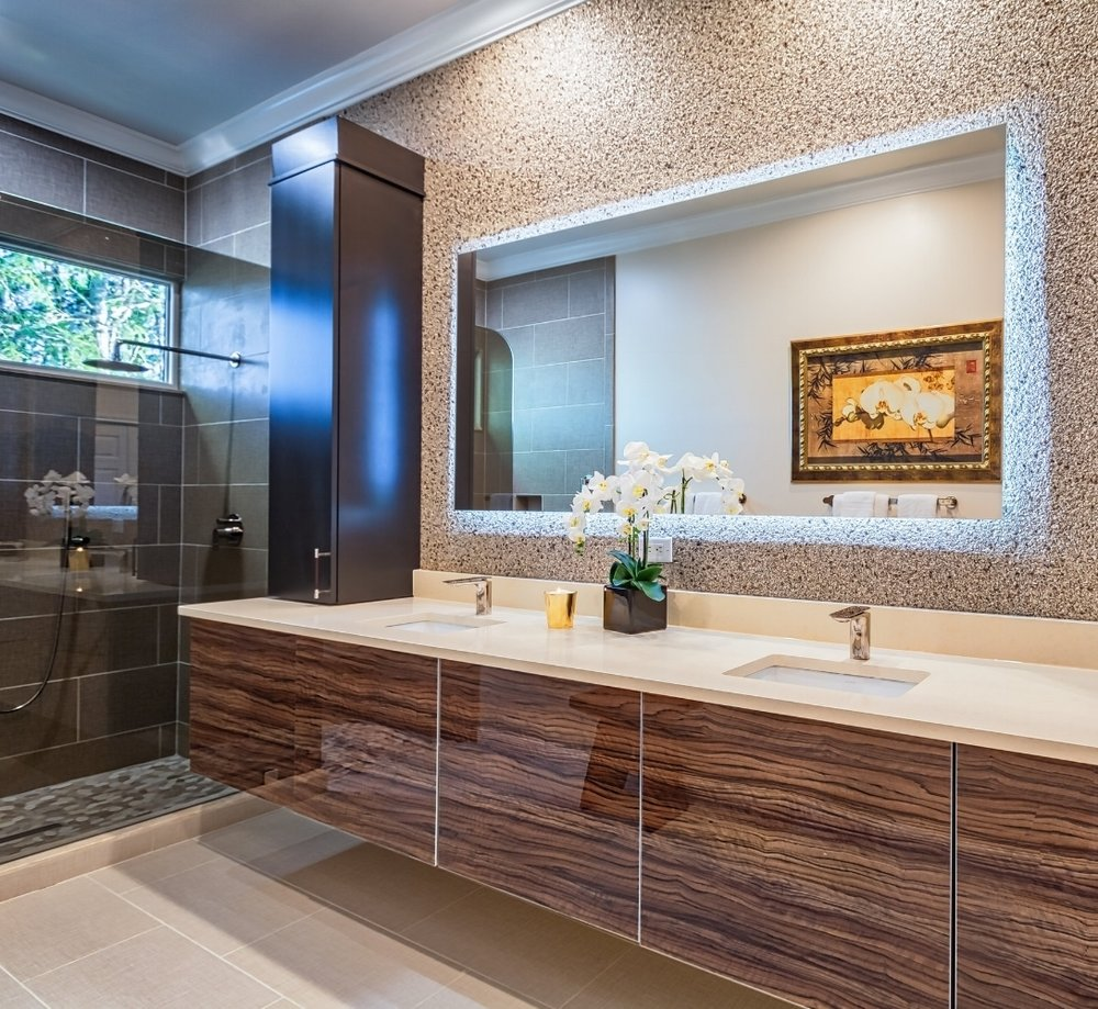 Total redo of this master bathroom with the goal of creating an Asian/Zen retreat for the owners. Quartz countertops, custom veneer vanity in tiger wood, mirror is lit from behind, wall covering, leather handles on cabinets. Flat tile with linen finish on floors. All photos by R.L. Caron. Courtesy of Diane Torrisi Designs.