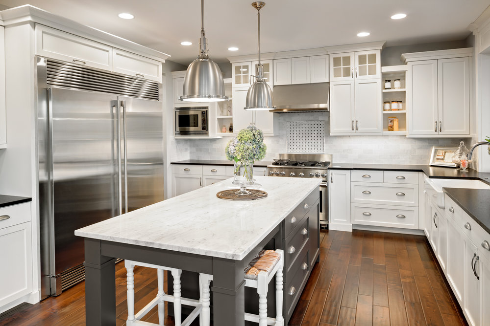 beautiful-white-kitchen-with-island--hardwood-floor-and-stainless-appliances-grey-island