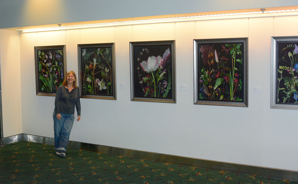 """Here I am in front of 5 of my pieces in the permanent collection of Port of Portland. Yes! That flower is bigger than my head! Each image is 26""""x32"""", in beautiful frames by local Joanne Rollins at Art of Framing."""