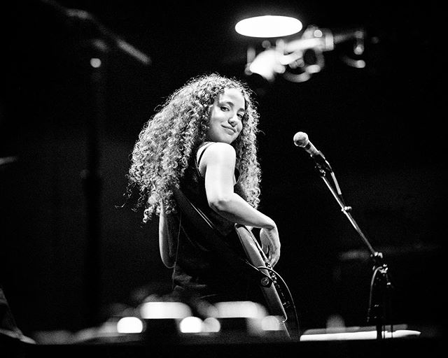 """Very proud of my buddy Tal Wilkenfeld for releasing her debut major label album """"Love Remains"""" on BMG USA today. I met Tal fifteen years ago when we were both kiddos in NYC, except she was a kid being touted as one of the most talented bass players in the world at 18 years old. It's been a joy to watch her career and talent grow and after a decade of backing some of the literally most talented musicians on the planet, she's now created something of her own to share with the world. • • • • • I was lucky enough to be in LA a few years ago to shoot some work of Tal warming up with her band before recording the album. This photo is my favorite of the bunch from the three days I spent with them. It's a photo I took for myself and never intended to deliver in an edit, Tal and the band had just finished practicing this sprawling cover of Jeff Buckley's """"Last Goodbye"""" and it sounded incredible, one of those moments where as a friend of Tal and a huge fan of Jeff Buckley I was just feeling this internal sense of """"YES!"""" cause it was so cool to see that firsthand. • • • • • Right after they finished the song, I was sitting on the back of the stage in front of the amp, just enjoying myself and not shooting at all. My camera was in my lap and Tal looked back at me and I said something to the effect of """"that was incredible, loved that"""" and she looked at me and smiled. This is that moment shot from my lap without looking through the lens, shot so I could remember it. When I saw the photo later on as I was editing I wrestled for a while with whether I wanted to include it, I love it, but it also felt more like a private thought that something you let go into the world. • • • • • Ultimately it felt right to let it go, and I'm happy I did since a lot of people seem to love it. So much so that people have drawn it as a sketch and done these crazy manipulations of it for fan accounts and that's kinda cool! In retrospect maybe that's as close I'll ever come to what putting out an album """
