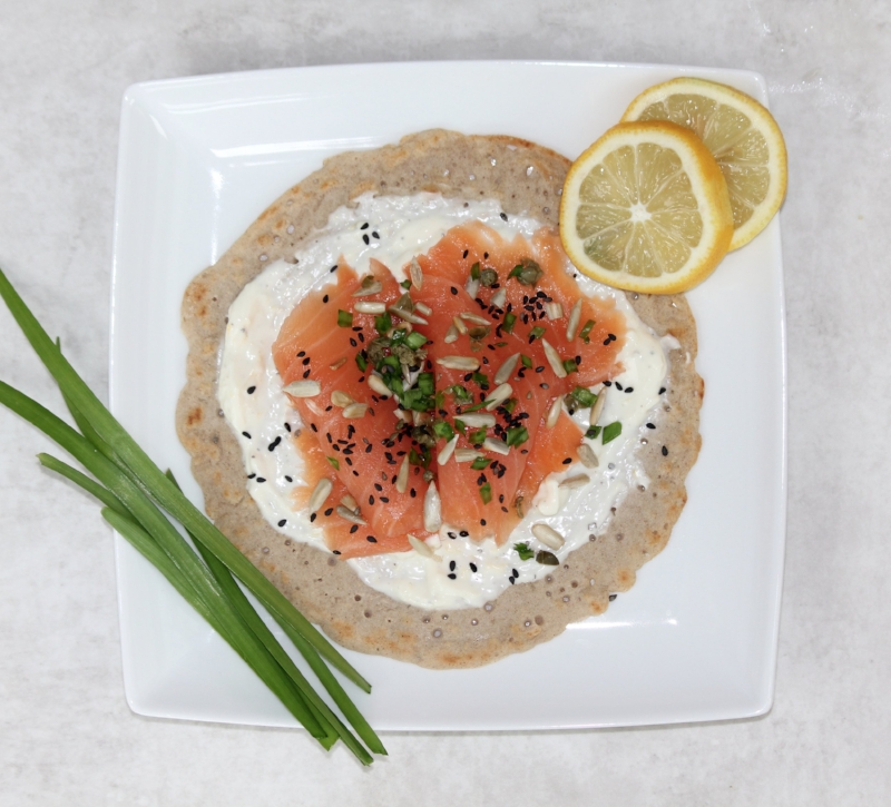 Buckwheat pancake with smoked salmon, lemon cream cheese, chives, capers and toasted seeds