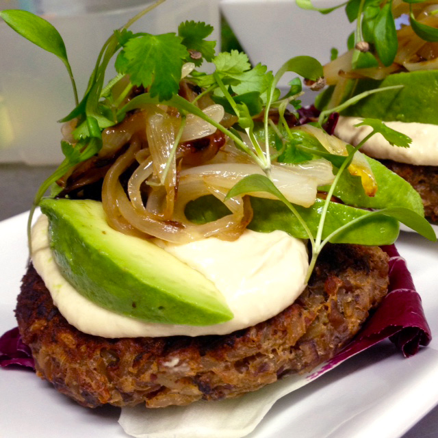 Open mushroom and brown rice burger on radicchio w sautéed onions, tahini, avocado & coriander