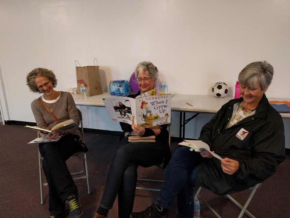 My wonderful volunteers trying to be serious and read as examples to the kids.