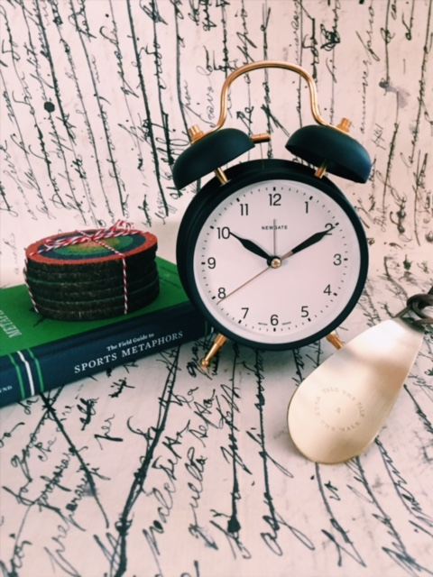 Classic matte green clock, a book of sports metaphors, colorful target coasters, and a sentimentally engraved shoe horn